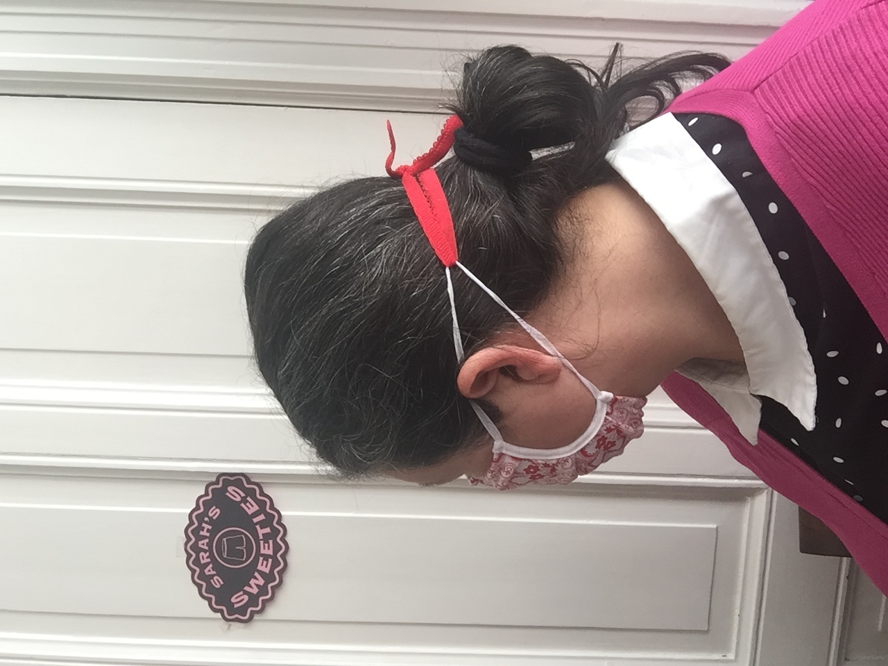 Foto van vrouw met snoetie #1 van de achterkant de oorelastieken zijn achter op haar hoofd naar elkaar toegetrokken met een rood stuk elastiek met een knoop erin
