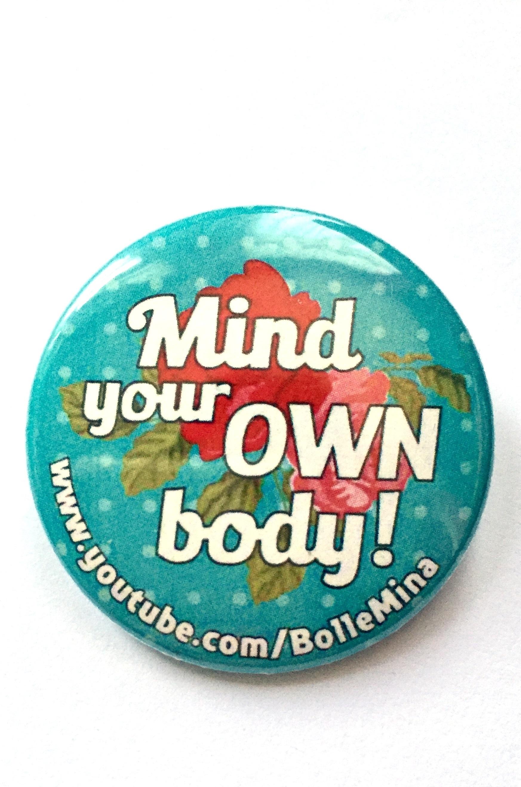Foto van een button mt een turquoise achtergrond met lichtblauwe stipjes. Hierop een grote rood roze roos en in witte letters de tekst Mind your own body